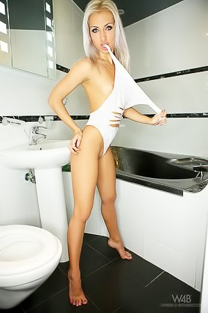 Blond-haired beauty dressed in white showing off her stunning body
