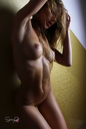 Busty blonde with teen a great fit body posing naked in the dark