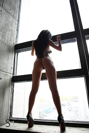 Busty brunette with a great body poses naked next to the window
