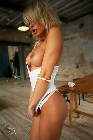 Short-haired blonde dressed in white posing next to the mirror