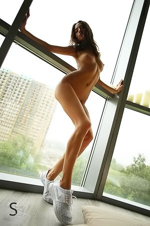 Leggy chick with white sneakers decides to get naked next to the window